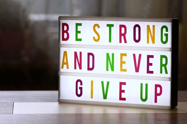 neon z kolorowym napisem: be strong and never give up